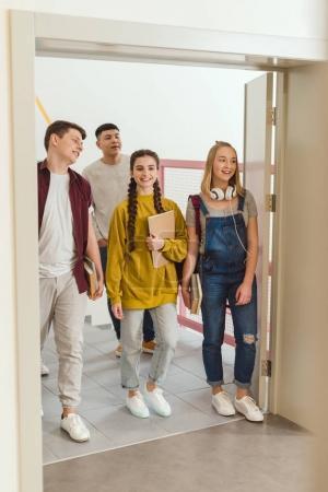 happy teenage high school students walking by school corridor