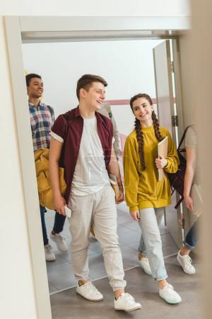 multiethnic group of high school students walking by school corridor on break