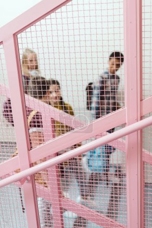 view through grid on group of high school students on stairs of school corridor