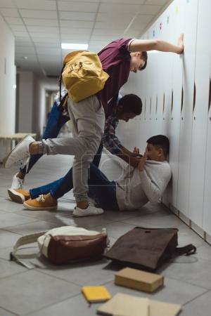 frightened asian schoolboy being bullied in school corridor