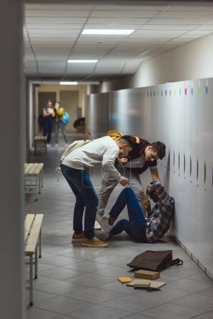 écolier victime de brimades de ses camarades de classe dans le couloir de l'école avec des écolières effrayés floues sur fond