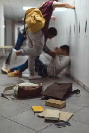 blurred shot of schoolboy being bullied by classmates in school corridor under lockers with spilled books from backpack on floor