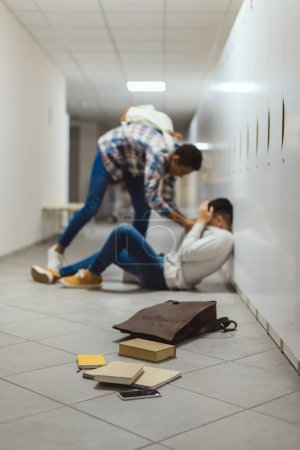 schoolboy being bullied by classmate in school corridor under lockers with spilled books from backpack on floor