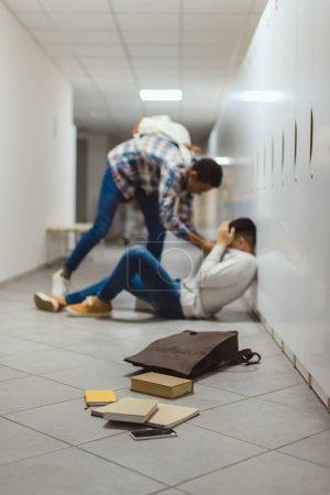 écolier victime d'intimidation par le camarade de classe dans le couloir de l'école sous les casiers avec déversé livres du sac à dos sur le plancher