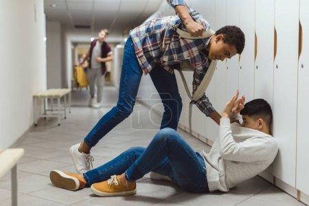 écolier peur victime d'intimidation par le camarade de classe à couloir d'école sous les casiers tandis que l'autre garçon en cours d'exécution pour l'aider