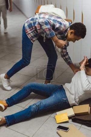 schoolboy being bullied by classmate in school corridor
