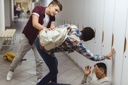 écoliers victime d'intimidation dans le couloir de l'école de leur camarade de classe