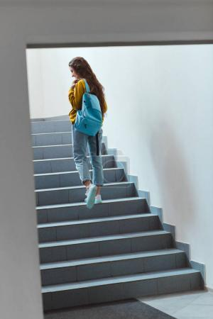 Photo for Rear view of schoolgirl with backpack walking upstairs - Royalty Free Image