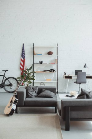 interior of modern living room with bicycle, guitar, american flag, laptop, shelves and armchairs