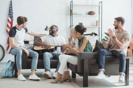 group of multiethnic smiling young people playing guitar in living room