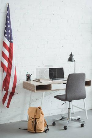 Photo pour Intérieur de la salle de séjour moderne avec un drapeau américain sur le mur de briques et table avec ordinateur portable - image libre de droit
