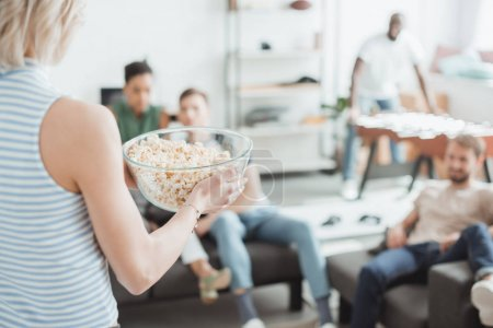 cropped image of woman with bowl of popcorn and her friends behind