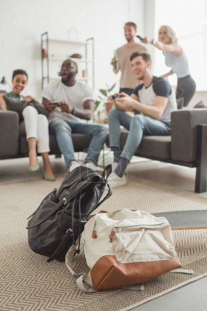 two backpacks and longboard on foreground and group of multiethnic friends with joysticks playing video game