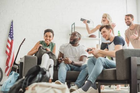 low angle view of happy multiethnic friends with joysticks playing video game