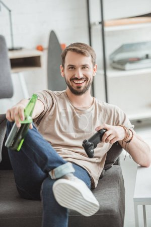 smiling young man sitting with beer bottle and joystick