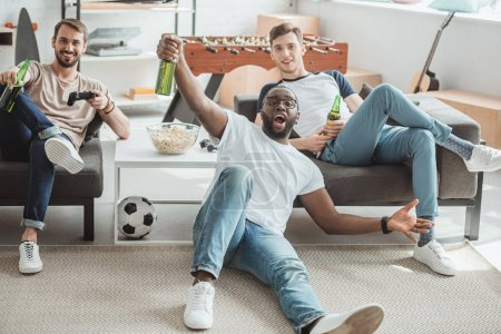 three multicultural young men in living room watching football match and celebrating with beer bottles