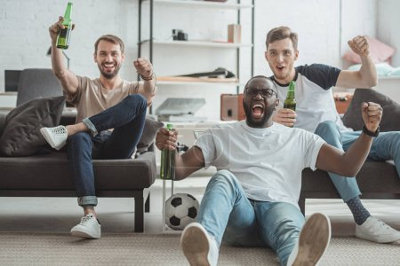 young happy multicultural male friends watching football match and celebrating with beer bottles in hands