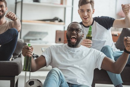 group of multicultural young men watching football match and celebrating with bottles of beer