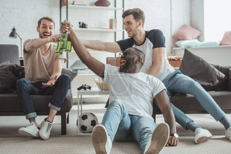 multiethnic young men watching football match and celebrating and clinking bottles of beer