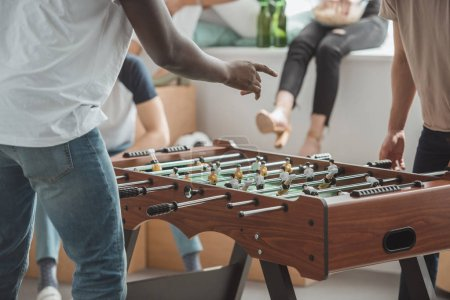 cropped image of man pointing by finger on table football board