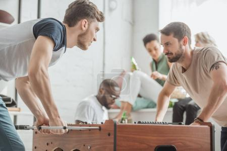 young men with facial expression playing table football with friends sitting behind