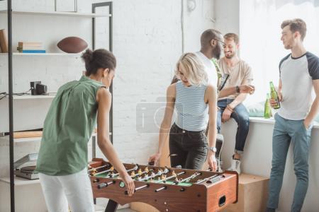 jeunes femmes jouer baby-foot avec des amis masculins debout derrière