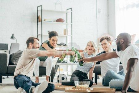 Photo pour Heureux amis multiethniques assis sur le plancher et cliquetis avec des bouteilles de bière - image libre de droit