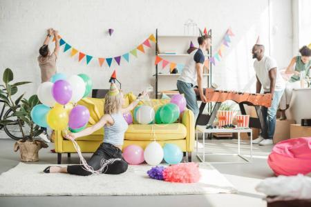 young woman sitting on floor with colorful balloons and her friends decorating room behind
