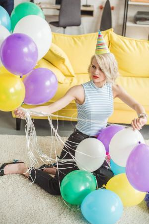 young attractive woman in party hat siting on floor with colorful balloons