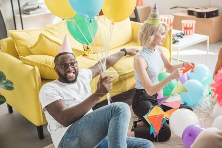 stylish african american man in eyeglasses and party hat holding colorful balloons in hand and young woman with party garlands sitting near