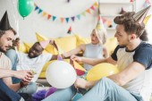 multiethnic friends in party hats sitting on floor with balloons in decorated room