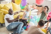 multicultural friends in party hats sitting on floor with balloons in decorated room