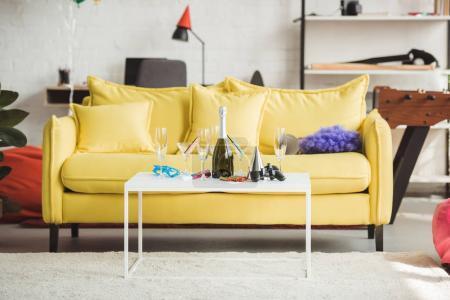Photo pour Intérieur moderne salon décoré avec bouteille de champagne, les verres, les fournitures de joystick et parti sur table - image libre de droit