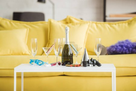 closeup shot of table with champagne, glasses, joystick and party supplies