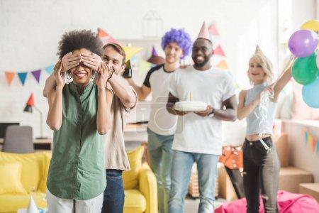Photo pour Jeunes hommes et femmes couvrant les yeux de la jeune amie et la saluant avec un gâteau d'anniversaire lors d'une fête surprise - image libre de droit