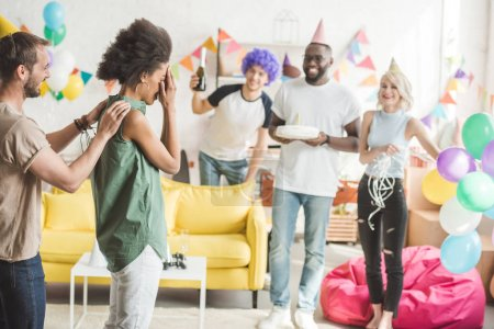 Young people covering eyes of young woman and greeting her with birthday cake  on surprise party
