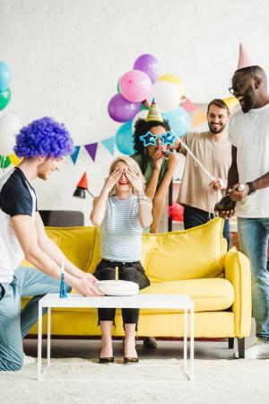 Photo for Happy friends greeting young woman with birthday cake on surprise party - Royalty Free Image