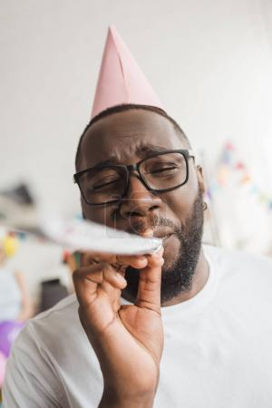 Happy african american in party hat blowing party horn