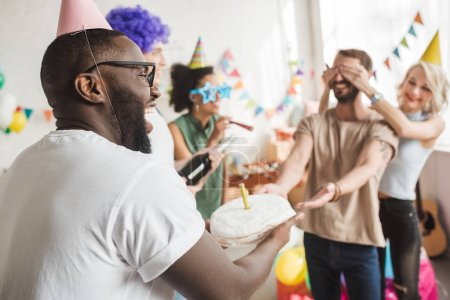 Photo for Happy friends covering eyes of young man and greeting him with birthday cake - Royalty Free Image