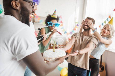 Photo for Partying diverse people covering eyes of young friend and greeting him with birthday cake - Royalty Free Image