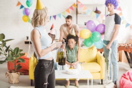 Blonde girl opening champagne in front of partying friends