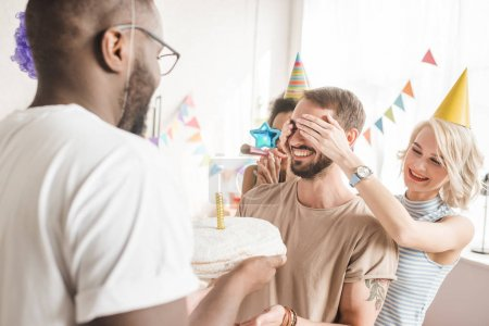Happy friends covering eyes of young man and greeting him with birthday cake