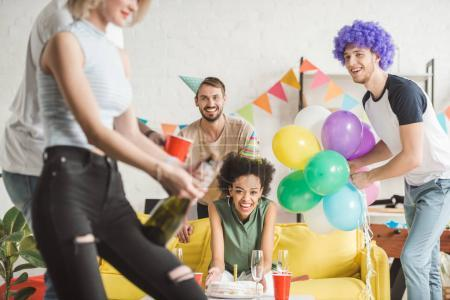 Cheerful young people looking at woman opening champagne at birthday party