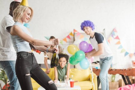 Blonde woman opening champagne in front of partying friends