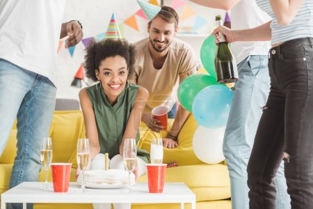 Photo for Happy young men and woman celebrating with champagne and birthday cake - Royalty Free Image