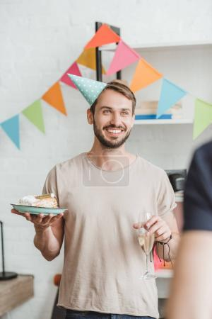 Smiling man in party hat holding plate with cake at home party