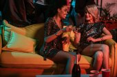 Young multiracial women celebrating with drinks in cozy room