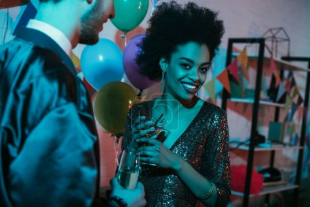 African american woman holding glass with cocktail and talking to man at party