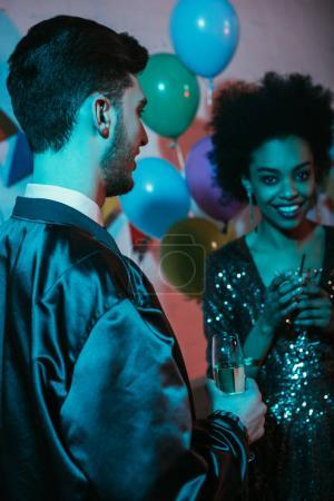Man and woman holding glasses and talking at party