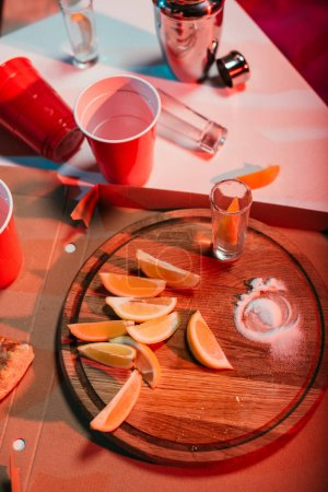 Top view of wooden board with oranges and party cups with drinks
